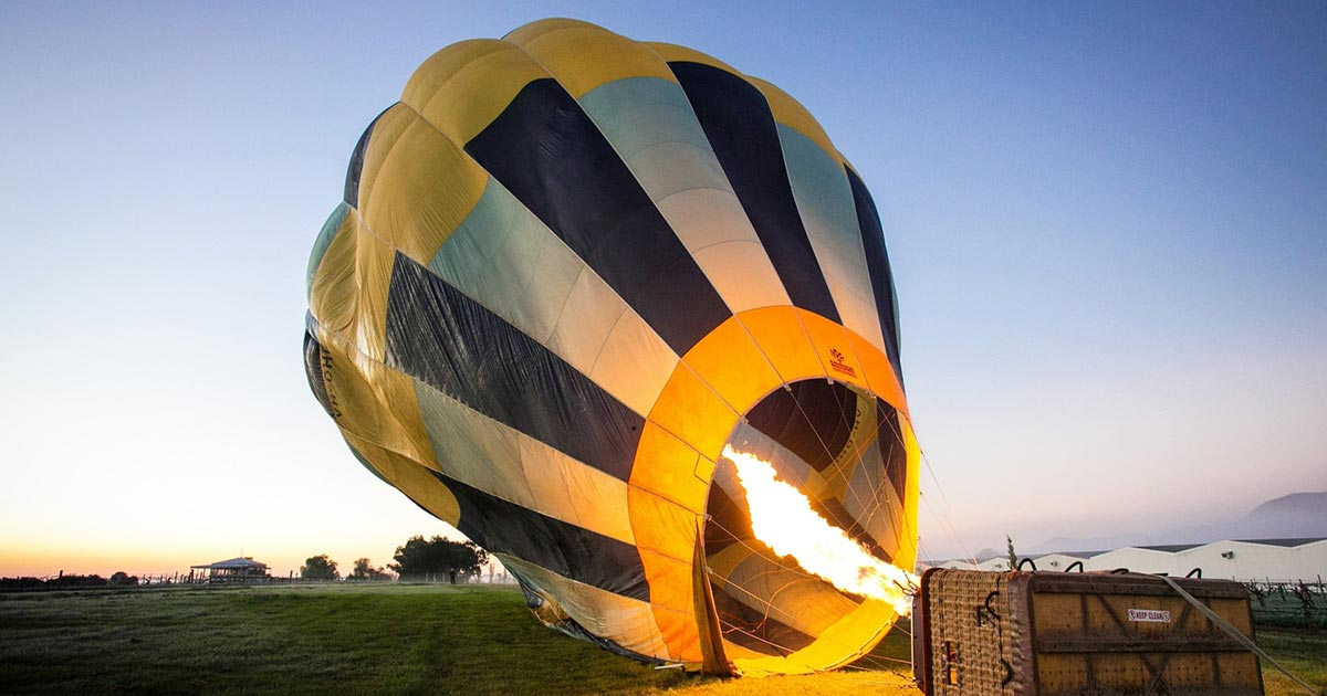 hot air balloon in a field about to take off